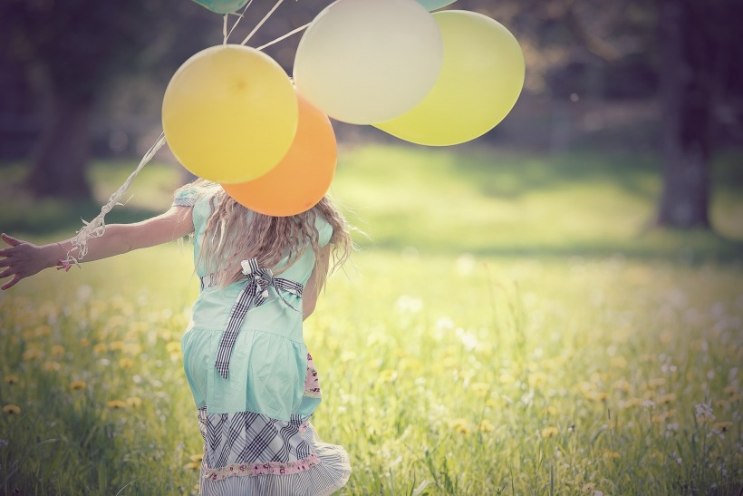 girl in grass with balloons